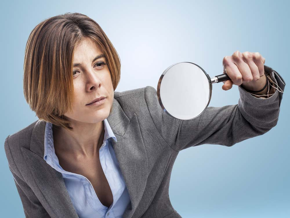 Business woman with magnifying glass.